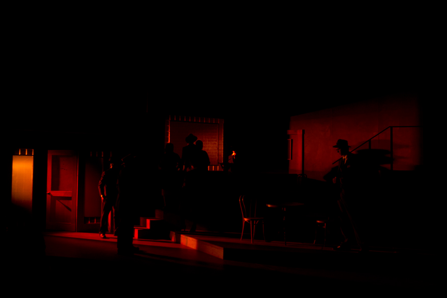 Gangsters in near darkness with touches of red light